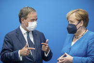 Armin Laschet, candidate for chancellor of Germany's center-right block of the Christian Union parties speaks with Chancellor Angela Merkel prior to a Christian Democratic Union party meeting in Berlin, Germany, Monday, Aug. 30, 2021. (Michael Kappeler/Pool Photo via AP)