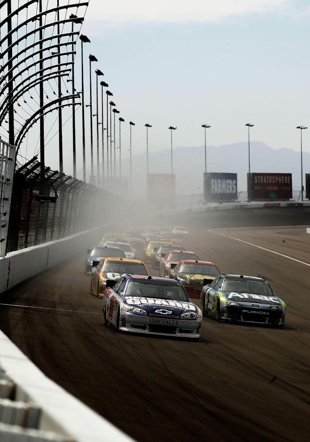 LAS VEGAS, NV - MARCH 11: Dale Earnhardt Jr., driver of the #88 National Guard/Diet Mountain Dew Chevrolet, and Carl Edwards, driver of the #99 Aflac Ford, lead a group of cars during the NASCAR Sprint Cup Series Kobalt Tools 400 at Las Vegas Motor Speedway on March 11, 2012 in Las Vegas, Nevada. (Photo by Todd Warshaw/Getty Images for NASCAR)