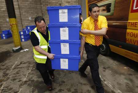 FILE PHOTO: Edinburgh City Council contractors carry boxes of postal ballots in a storage warehouse in Edinburgh, Scotland May 5, 2010. REUTERS/David Moir/File Photo