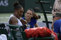 Serena Williams, left, speaks with trainers before retiring with a medical issue during her match against Garbine Muguruza, of Spain, at the BNP Paribas Open tennis tournament Sunday, March 10, 2019, in Indian Wells, Calif. (AP Photo/Mark J. Terrill)