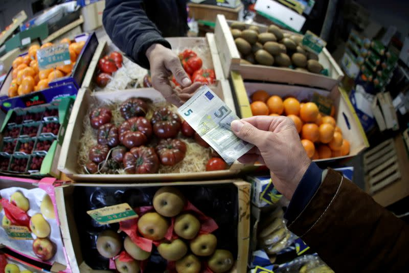 FILE PHOTO: A shopper pays with a Euro bank note in a market in Nice