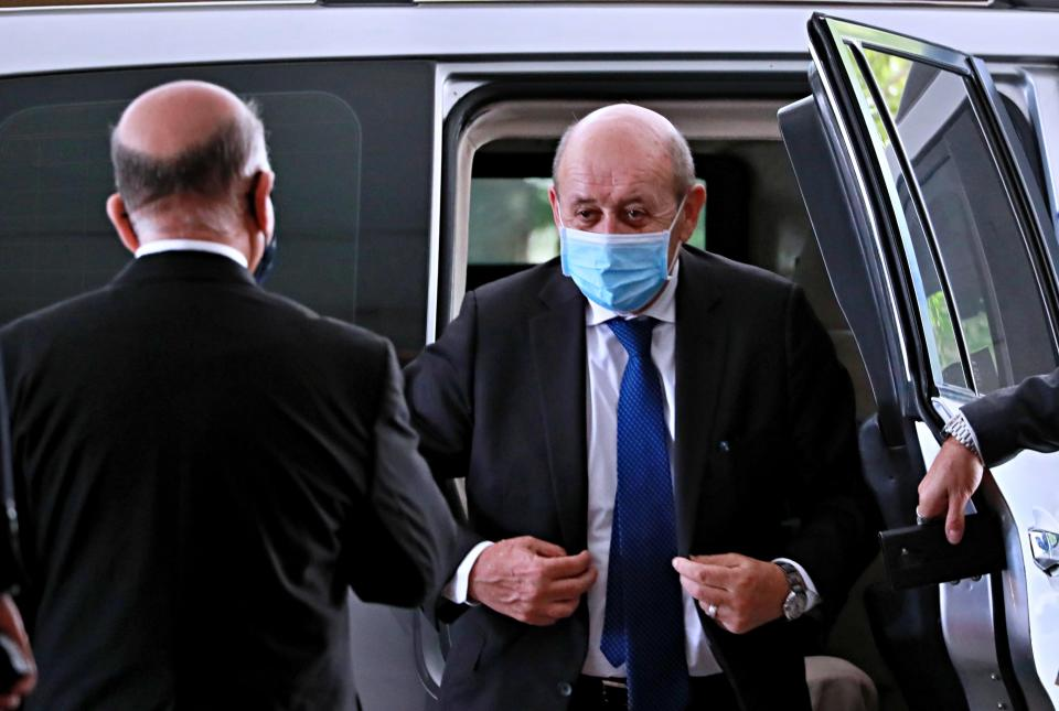 French Foreign Minister Jean-Yves Le Drian, right, wearing a mask to help prevent the spread of the coronavirus, arrives to meet his Iraqi counterpart Fouad Hussein, left, in Baghdad, Iraq, Thursday, July 16, 2020. (AP Photo/Hadi Mizban)