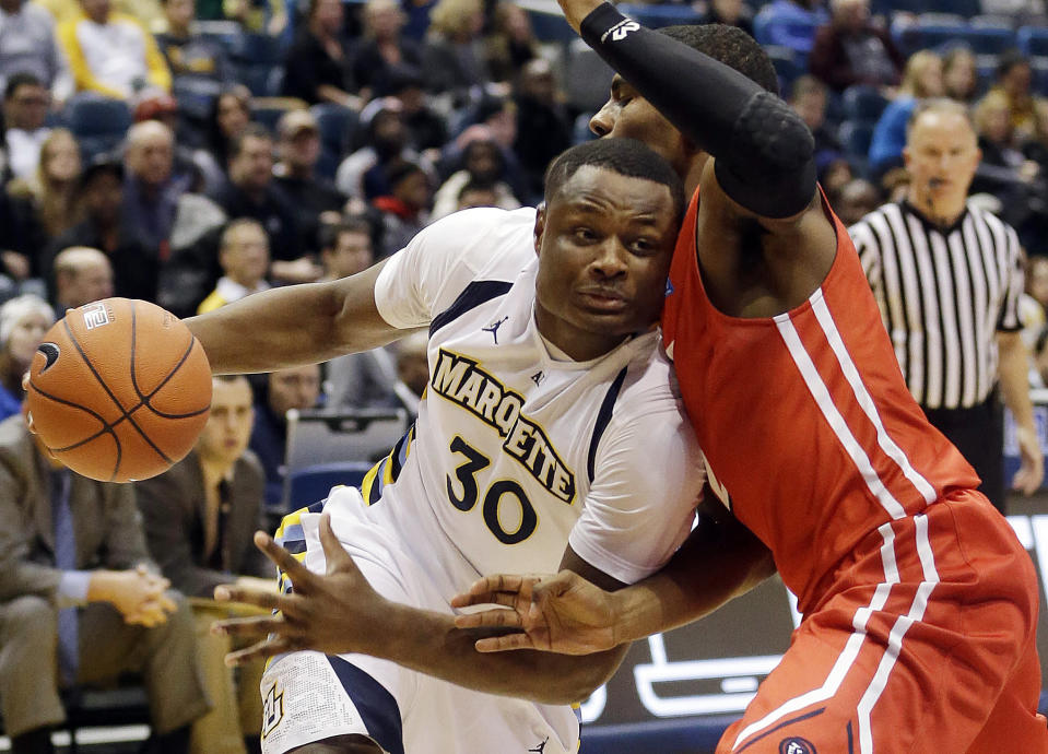 Marquette's Deonte Burton, left, tries to drive past N.J.I.T.'s Tim Coleman during the first half of an NCAA college basketball game Monday, Nov. 24, 2014, in Milwaukee. (AP Photo/Morry Gash)