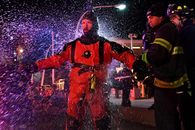 A FDNY rescue diver is hosed off with fresh water after pulling victims from a submerged helicopter after it crashed into the East River in New York, U.S., March 11, 2018. REUTERS/Darren Ornitz