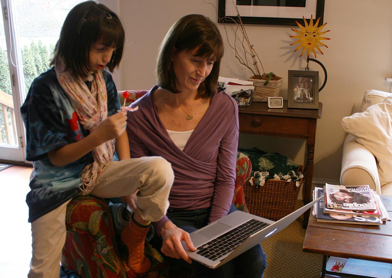 "In this Feb. 22, 2012 photo, Clara Beatty, 9, looks at her childhood photos on a computer with her mother, Janet Beatty, at their home in Winnetka, Ill. Clara was born with facial deformities caused by a genetic mutation called Treacher Collins syndrome. However, she is a typical fourth-grader in every other way. Her parents discovered Clara was quite able to cope, sometimes better than they. Even today, her mother, Janet Beatty, is astounded at how well her youngest daughter navigates the world. ""Even when she was little, you could look at her and people would say there's an old soul in there,"" she says. ""She just had these big eyes and you could see her taking everything in."" (AP Photo/Martha Irvine)"
