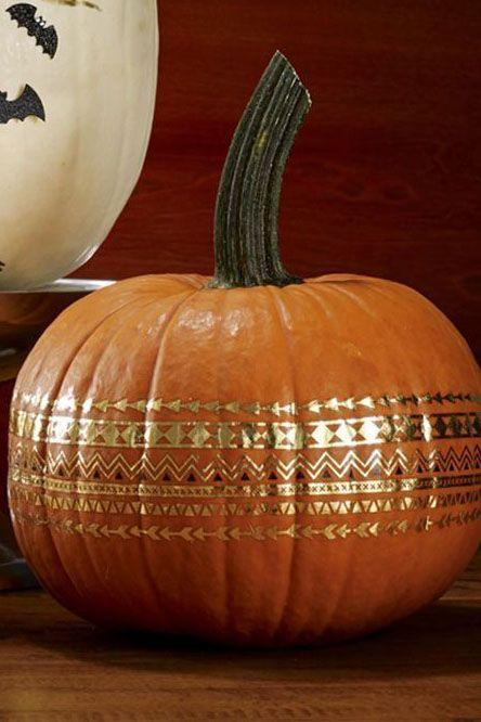 """<p>Clean and dry small-to-medium round pumpkin. Apply per instructions on premium metallic tattoos. Or you can wrap ¼-inch-wide copper foil tape to a small pumpkin. Cut strips in half lengthwise as needed to lie flat. </p><p><a class=""""link rapid-noclick-resp"""" href=""""https://www.amazon.com/Temporary-Metallic-WffDirect-Waterproof-Stickers/dp/B076MNMTPH/?tag=syn-yahoo-20&ascsubtag=%5Bartid%7C10070.g.331%5Bsrc%7Cyahoo-us"""" rel=""""nofollow noopener"""" target=""""_blank"""" data-ylk=""""slk:SHOP TEMPORARY TATTOOS"""">SHOP TEMPORARY TATTOOS</a></p>"""