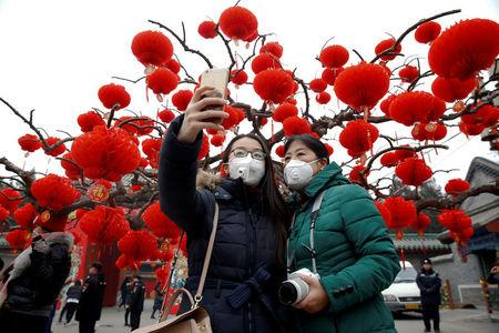 FILE PHOTO: Visitors wearing face masks against pollution take pictures of themselves at the temple fair at Ditan Park (the Temple of Earth) as the Lunar New Year of the Rooster is celebrated, in Beijing, China January 28, 2017. REUTERS/Damir Sagolj/File Photo