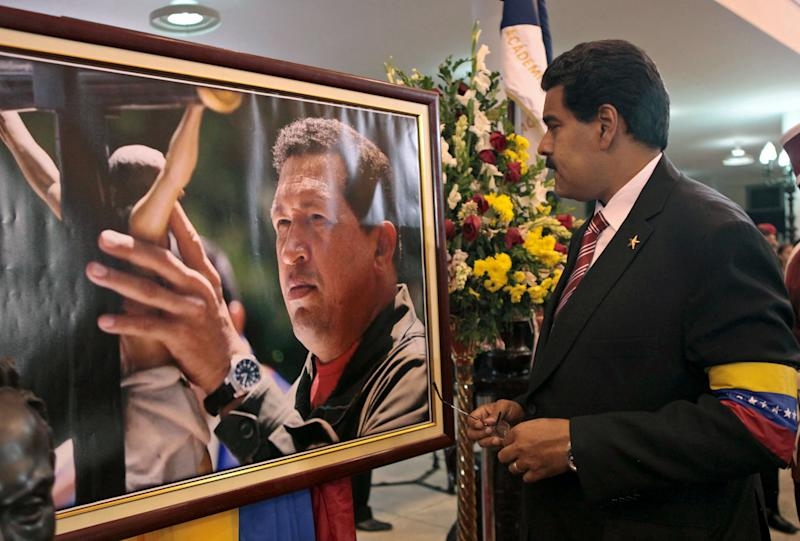 FILE - In this March 8, 2013 file photo released by Miraflores Press Office, Venezuela's acting President Nicolas Maduro stands in front of a portrait of Venezuela's late President Hugo Chavez after a symbolic swearing in ceremony in the presence of the flag-draped coffin of Chavez at the military academy where the funeral ceremony was held earlier in Caracas, Venezuela. For his loyal followers, Chavez was already a living legend on par with independence era hero Simon Bolivar even before his March 5 death from cancer. In a mere three weeks, however, Chavez has ascended to divine status, at least according to political rhetoric, as the government and his die-hard loyalists build a religious mythology around him ahead of April 14 elections scheduled to pick a new leader. (AP Photo/Miraflores Press Office, File)