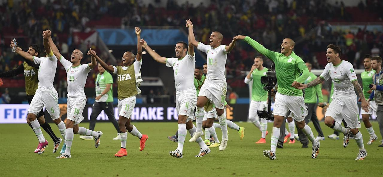 Algerian players run to their supporters to celebrate after the group H World Cup soccer match between South Korea and Algeria at the Estadio Beira-Rio in Porto Alegre, Brazil, Sunday, June 22, 2014. Algeria won the match 4-2.   (AP Photo/Martin Meissner)