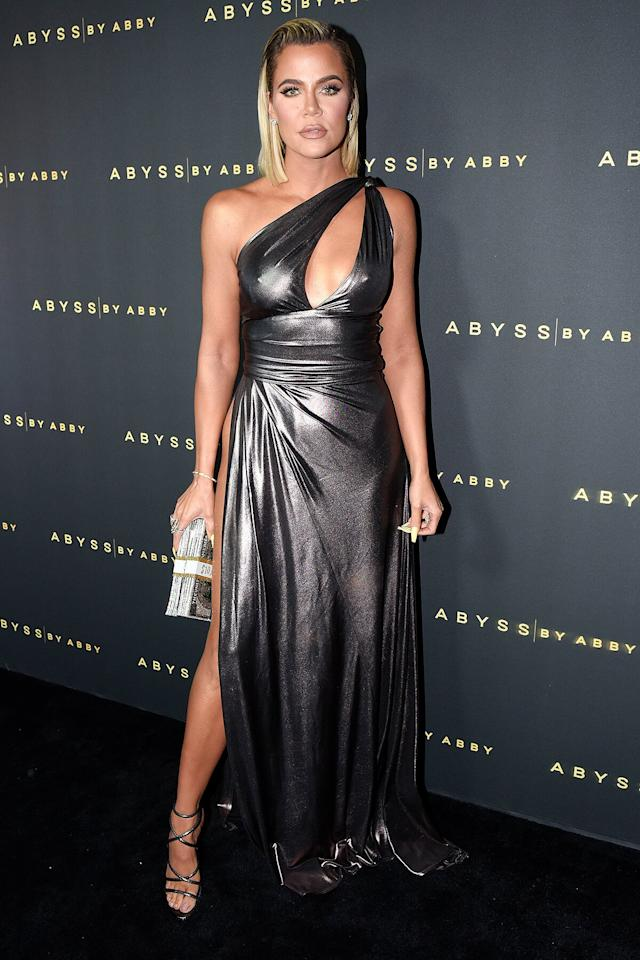 in aAbyss by Abby metallic silver one-shoulder gown, featuring a high slit, keyhole detail an a cinched waist, paired with strappy metallic heels and an embellished money clutch at the Abyss by Abby Arabian Nights Collection Launch Party in L.A.