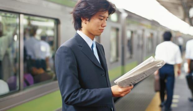 Businessman reading newspaper on railway station, side view