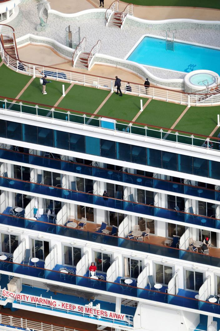 In this aerial image, health officials spray antiseptic on the deck of the Diamond Princess cruise ship walk on the deck as it remains quarantined at the Daikoku Futo pier at Yokohama Port on February 7, 2020.