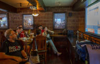 A group of U.S. Democrats supporters gather at a roadhouse restaurant to view U.S. media coverage of the U.S. presidential election in Bangkok, Thailand, Wednesday, Nov. 4, 2020. (AP Photo/Gemunu Amarasinghe)