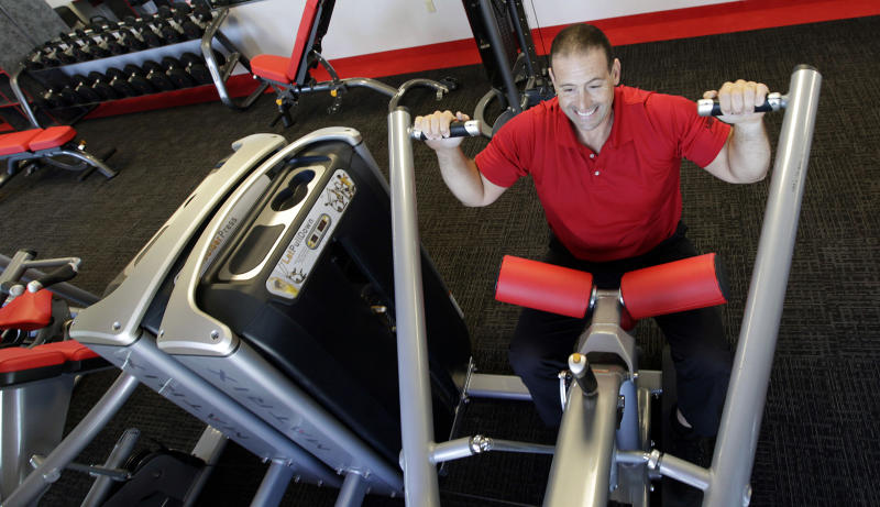 In this June 14, 2012, photo, gym manager Rick Limitone demonstrates a work out machine at a Snap Fitness truck stop gym in Dallas. From trucking companies embracing wellness and weight-loss programs to gyms being installed at truck stops, momentum has picked up in recent years to help those who make their living driving big rigs get into shape. (AP Photo/LM Otero)