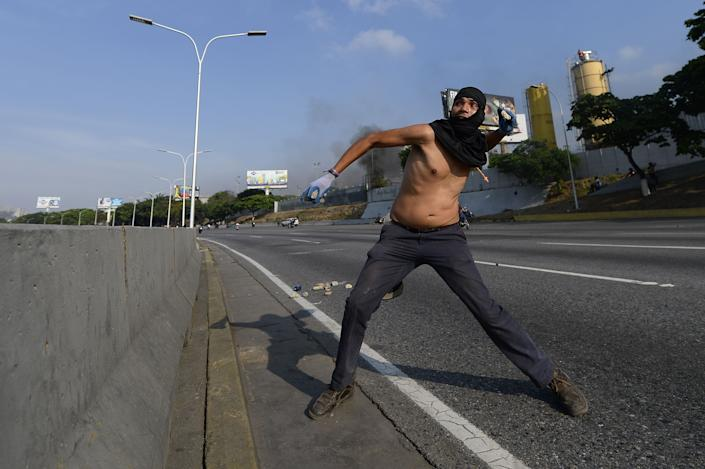 A supporter of Venezuelan opposition leader Juan Guaido clashes with security forces in Caracas on April 30, 2019. - Venezuelan opposition leader and self-proclaimed acting president  Juan Guaido said on Tuesday that troops had joined his campaign to oust President Nicolas Maduro as the government vowed to put down what it said was an attempted coup. (Photo by Matias Delacroix / AFP) / The erroneous mention[s] appearing in the metadata of this photo by Matias Delacroix has been modified in AFP systems in the following manner: [A supporter of Venezuelan opposition leader Juan Guaido] instead of [A Venezuelan]. Please immediately remove the erroneous mention[s] from all your online services and delete it (them) from your servers. If you have been authorized by AFP to distribute it (them) to third parties, please ensure that the same actions are carried out by them. Failure to promptly comply with these instructions will entail liability on your part for any continued or post notification usage. Therefore we thank you very much for all your attention and prompt action. We are sorry for the inconvenience this notification may cause and remain at your disposal for any further information you may require. (Photo: Matias Delacroix /AFP/Getty Images)