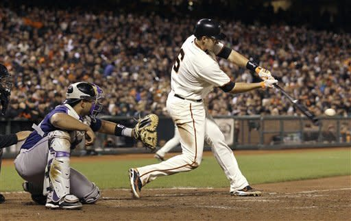 San Francisco Giants' Brett Pill (6) singles off of Colorado Rockies pitcher Matt Belisle to score Joaquin Arias during the eighth inning of a baseball game in San Francisco, Monday, May 14, 2012. Pictured at left is Rockies catcher Wilin Rosario. (AP Photo/Jeff Chiu)