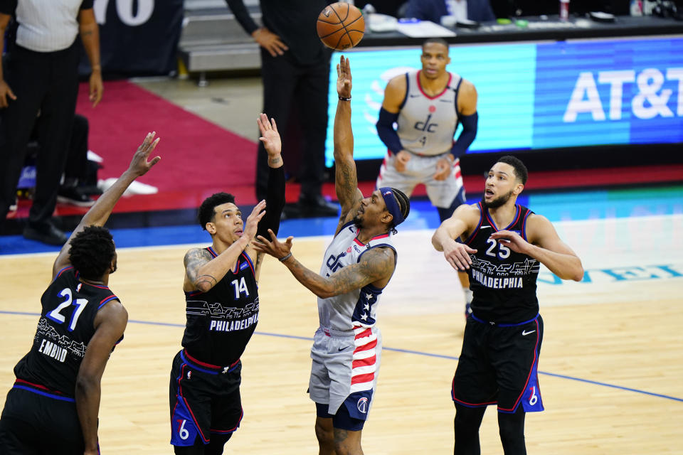 Washington Wizards' Bradley Beal (3) goes up for a shot against Philadelphia 76ers' Ben Simmons (25), Danny Green (14) and Joel Embiid (21) during the second half of Game 1 of a first-round NBA basketball playoff series, Sunday, May 23, 2021, in Philadelphia. (AP Photo/Matt Slocum)