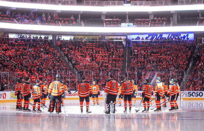 Edmonton Oilers gather around center ice before the team's NHL hockey game against the Vancouver Canucks on Wednesday, Oct. 13, 2021, in Edmonton, Alberta. (Jason Franson/The Canadian Press via AP)