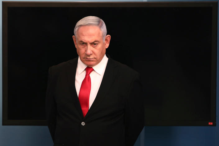 FILE - In this Saturday, March 14, 2020 file photo, Israeli Prime Minister Benjamin Netanyahu arrives for a speech from his Jerusalem office, saying Israel's restaurants and places of entertainment will be closed to stop the spread of the coronavirus. With the Israeli government enacting a series of emergency measures to stem the spread of the virus, critics are increasingly bemoaning that Israel's caretaker Prime Minister Netanyahu is exploiting the crisis to entrench himself in power and undermining the country's democratic foundations. (Gali Tibbon/Pool via AP, File)