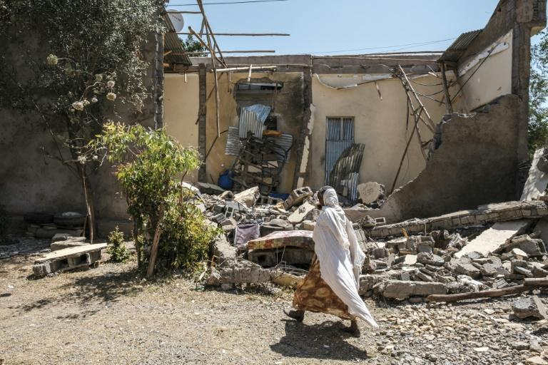 A woman walks in front of a damaged house in Wukro in the Tigray region on March 1