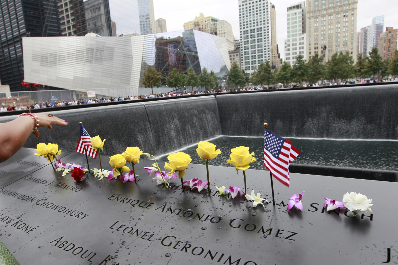 Flowers and American flags are arranged on the north pool of the National September 11 Memorial during a ceremony marking the 10th anniversary of the attacks at the World Trade Center, Sunday, Sept. 11, 2011 in New York. (AP Photo/Mary Altaffer)
