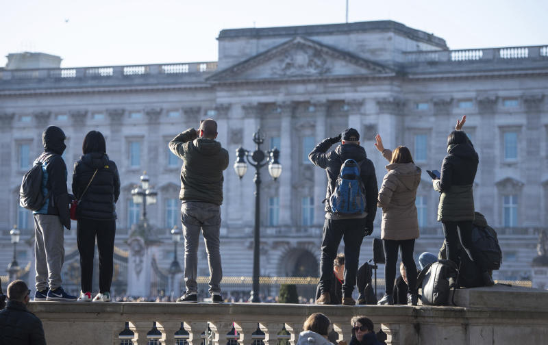 "Tourists take photos outside the gates of Buckingham Palace, following a statement by Britain's Queen Elizabeth II and Buckingham Palace, in London, Sunday, Jan, 19, 2020. Buckingham Palace says Prince Harry and his wife, Meghan, will no longer use the titles ""royal highness"" or receive public funds for their work under a deal that allows them to step aside as senior royals.  (Dominic Lipinski/PA via AP)"
