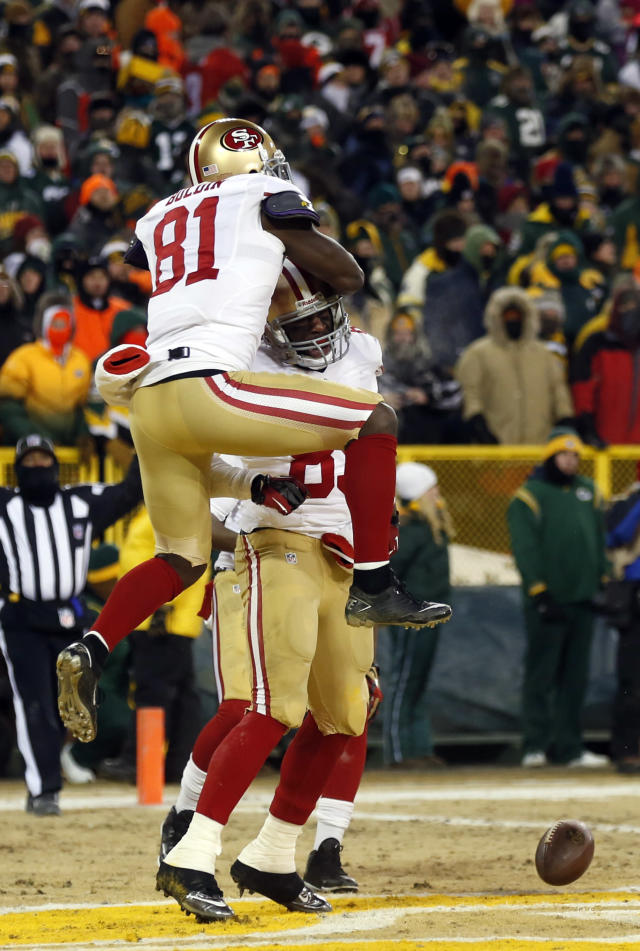 San Francisco 49ers wide receiver Anquan Boldin (81) jumps on tight end Vernon Davis (85) after Davis makes a touchdown catch during the second half of an NFL wild-card playoff football game against the Green Bay Packers, Sunday, Jan. 5, 2014, in Green Bay, Wis. (AP Photo/Jeffrey Phelps)