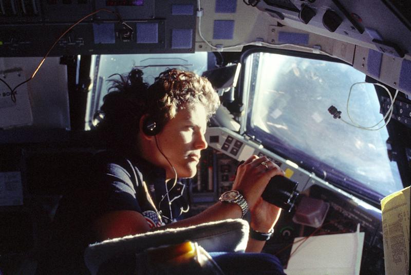 Astronaut Kathryn D. Sullivan, 41-G mission specialist, uses binoculars for a magnified viewing of Earth through Challenger's forward cabin windows on Oct. 6, 1984. (Johnson Space Center / NASA)