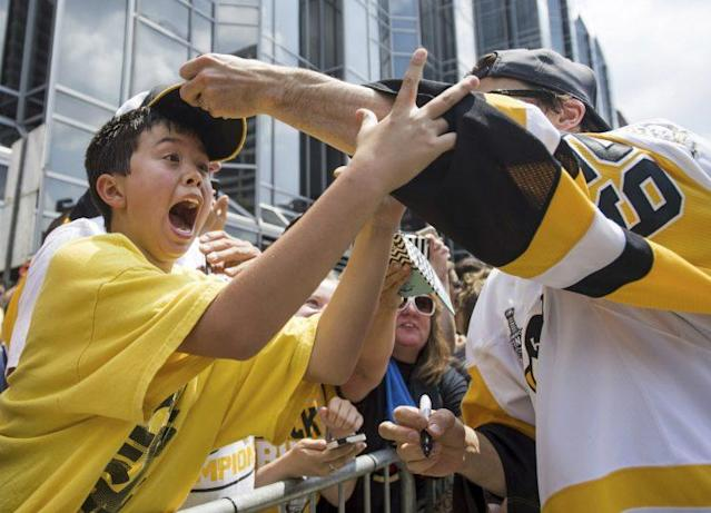 Pittsburgh Penguins Marc-Andre Fleury places a hat on the head of a young fan during the team's Stanley Cup NHL hockey victory parade on Wednesday, June 14, 2017, in Pittsburgh.(Steph Chambers/Pittsburgh Post-Gazette via AP)