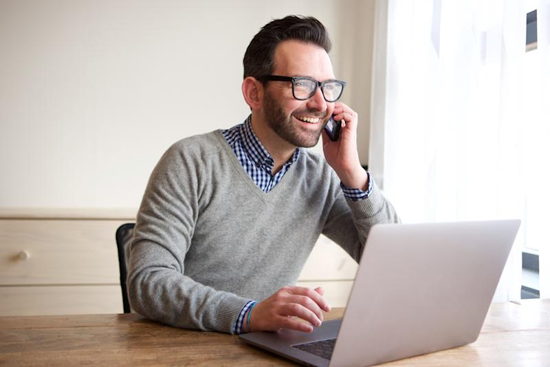 Man sitting at table with open laptop, smiling while holding phone to his ear