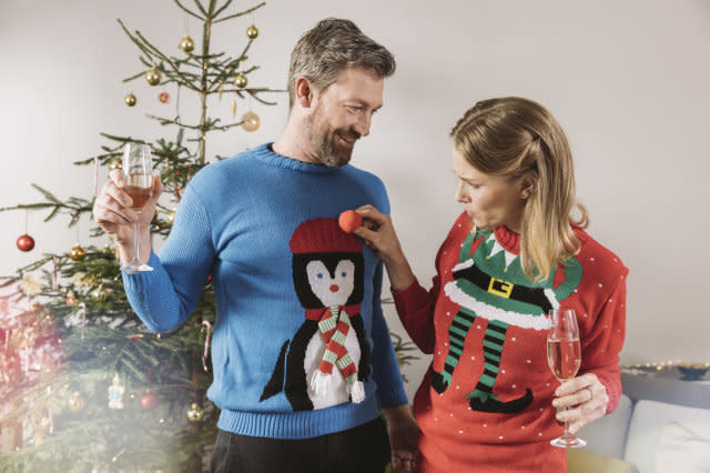 Two people with ugly Christmas sweaters laughing in front of tree