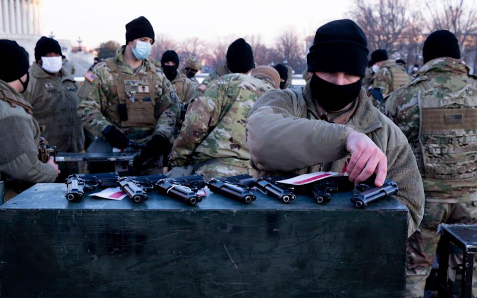 Firearms are issued to US National Guard troops at the East Front of the US Capitol - MICHAEL REYNOLDS/EPA-EFE/Shutterstock/Shutterstock