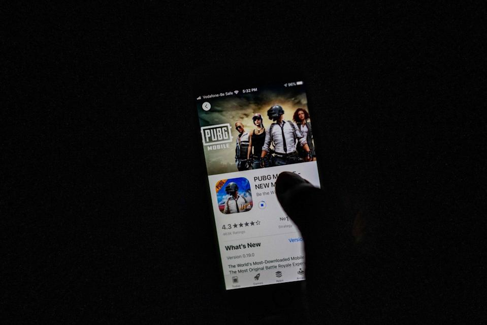 A man looks at Tencent Holdings' PUBG Mobile game on a smartphone. Users of mobile gaming apps in China are only required to provide their phone number to access these services, according to new rules released by Beijing. Photo: Agence France-Presse
