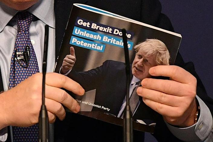 The Conservatives' election manifesto, brandished here by Boris Johnson, has at its core the 'Get Brexit Done' mantra (AFP Photo/Daniel LEAL-OLIVAS)