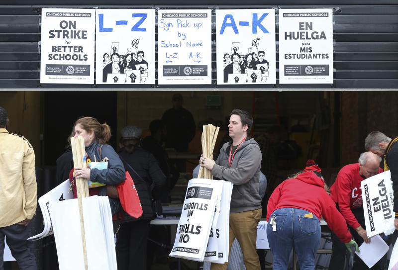 Chicago Teachers Union members pick up picket signs ahead of the pending strike at the CTU Center, Wednesday, Oct. 16, 2019, in Chicago. Chicago parents and community groups are scrambling to prepare for a massive teachers' strike set to begin Thursday, prompting the city to preemptively cancel classes in the nation's third-largest school district. (John J. Kim/Chicago Tribune via AP)