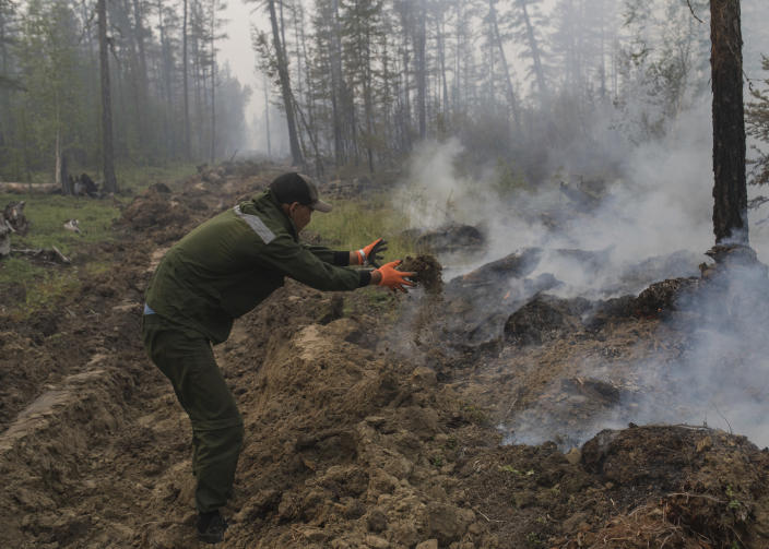 FILE - In this Sunday, July 18, 2021 file photo, a volunteer throws the earth to smother a forest fire outside Magaras village 87 km. (61 miles) west of Yakustk, the capital of the republic of Sakha also known as Yakutia, Russia Far East. Each year, thousands of wildfires engulf wide swathes of Russia, destroying forests and shrouding broad territories in acrid smoke. This summer has seen particularly massive fires in Yakutia in northeastern Siberia following unprecedented heat. (AP Photo/Alexey Vasilyev, File)
