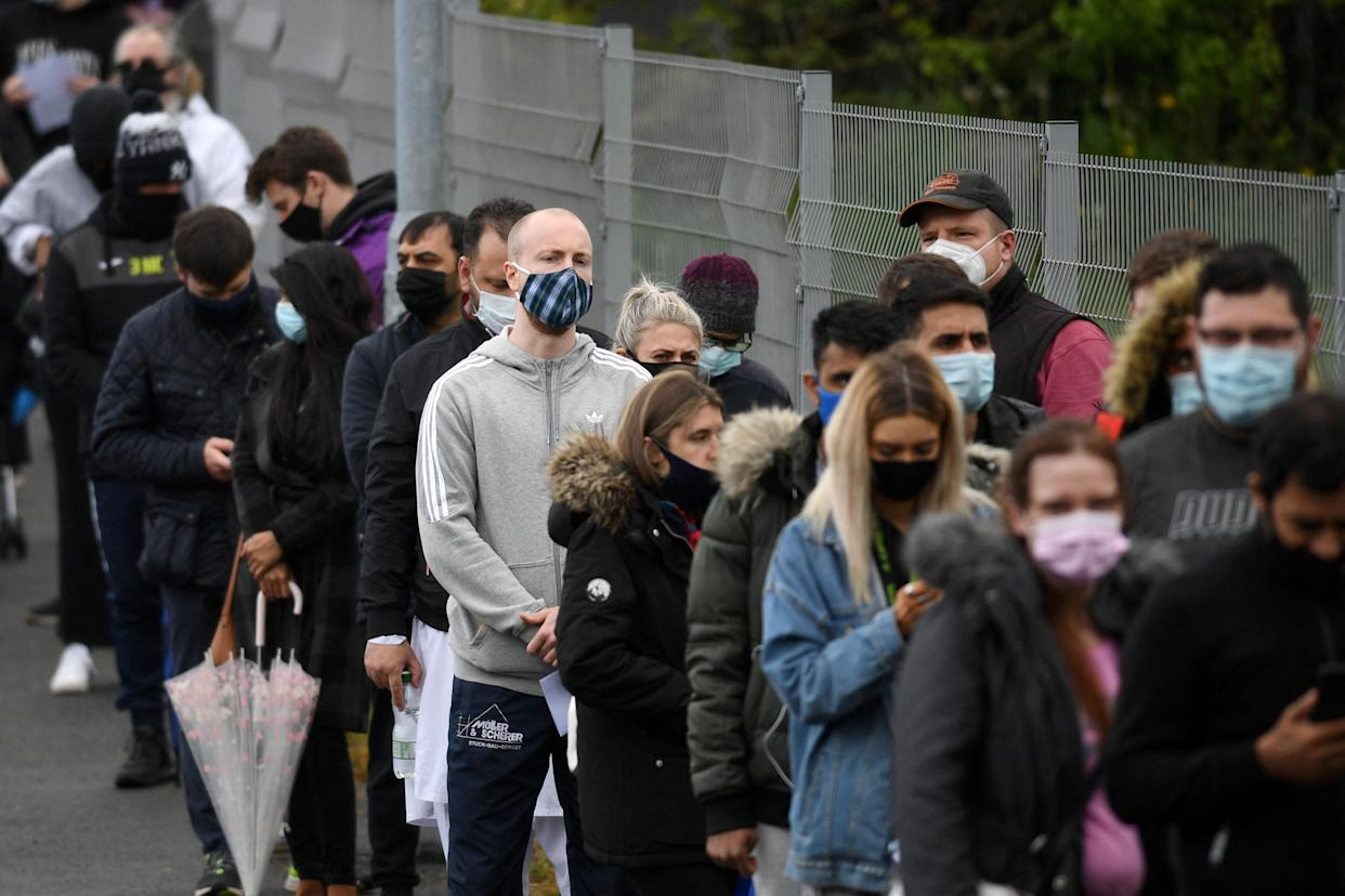 Members of the public queue to receive a Covid-19 vaccine at a temporary vaccination centre at the Essa academy in Bolton, northwest England on May 17, 2021. - England remains on track for the latest easing of its coronavirus lockdown next week but is taking no chances after a doubling of cases of an Indian variant, the government said today. (Photo by Oli SCARFF / AFP) (Photo by OLI SCARFF/AFP via Getty Images)