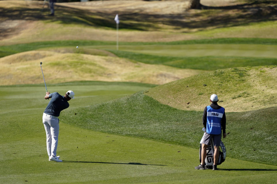 Tony Finau, left, hits from the third fairway during the final round of The American Express golf tournament on the Pete Dye Stadium Course at PGA Wes,t Sunday, Jan. 24, 2021, in La Quinta, Calif. (AP Photo/Marcio Jose Sanchez)