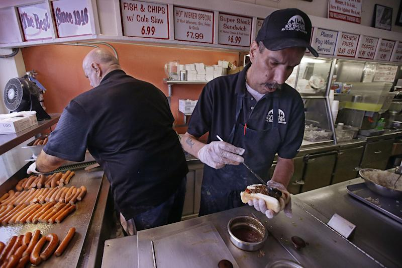 "In this Monday, March 3, 2014 photo, manager Jimmy Saccoccio, left, works the grill as Sal O'Brien preps a hot wiener ""all the way"" at Olneyville New York System of Providence in Providence, R.I. The James Beard Foundation named the Rhode Island restaurant one of five ""American Classics"". (AP Photo/Stephan Savoia)"