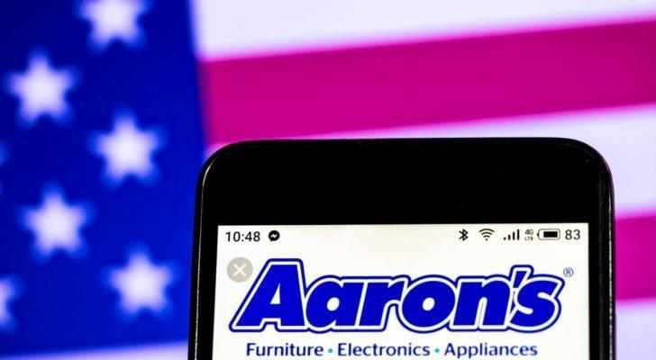 The logo for Aaron's (AAN) is displayed on a smartphone screen with an American flag in the background.