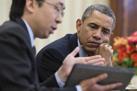 File handout photo of U.S. President Obama watches as CTO Park shows information on a tablet during a meeting in the Oval Office in Washington