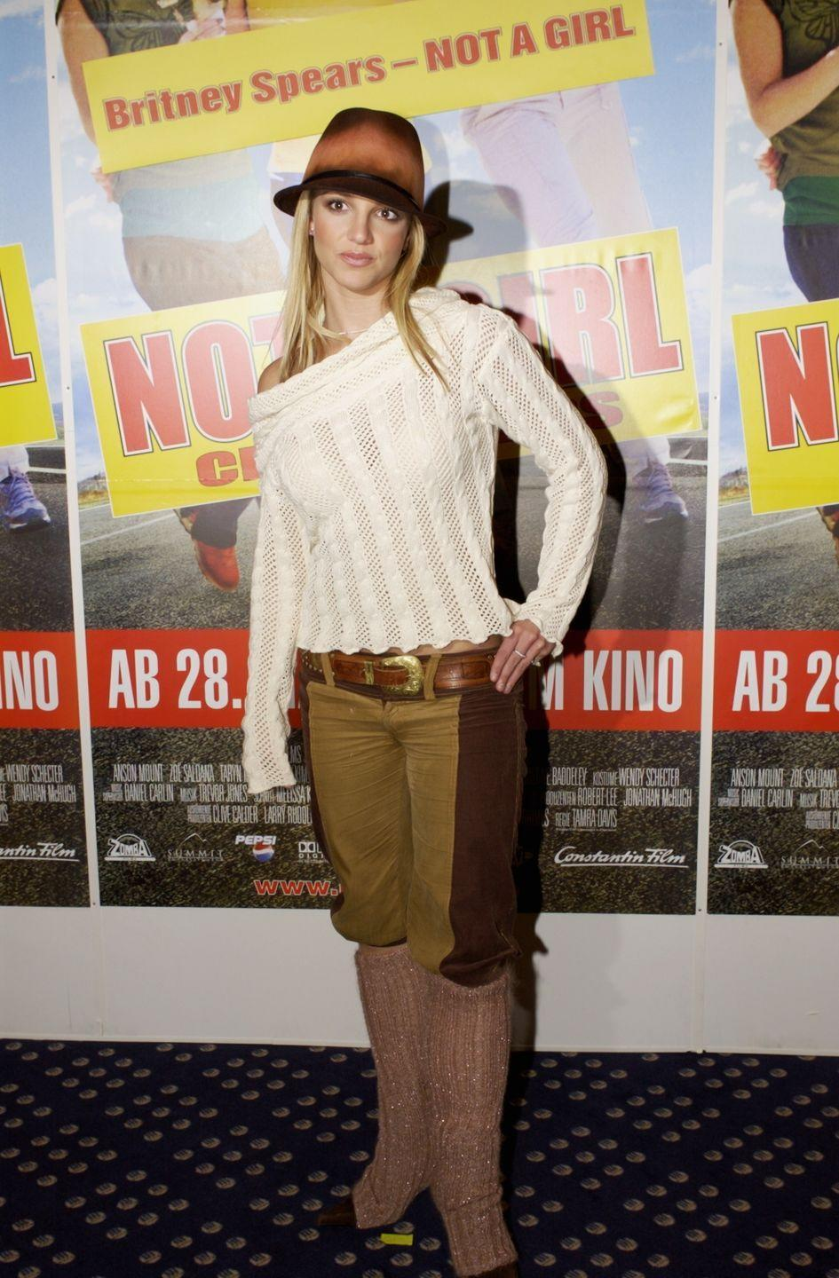 <p>Here, Britney wears a one-shoulder sweater, low-rise pants tucked into her knee-high boots, and her now-signature fedora hat.</p>