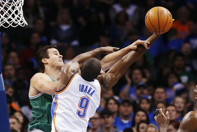 Boston Celtics forward Kris Humphries, left, and Oklahoma City Thunder forward Serge Ibaka (9) reach for a rebound in the first quarter of an NBA basketball game in Oklahoma City, Sunday, Jan. 5, 2014. (AP Photo/Sue Ogrocki)