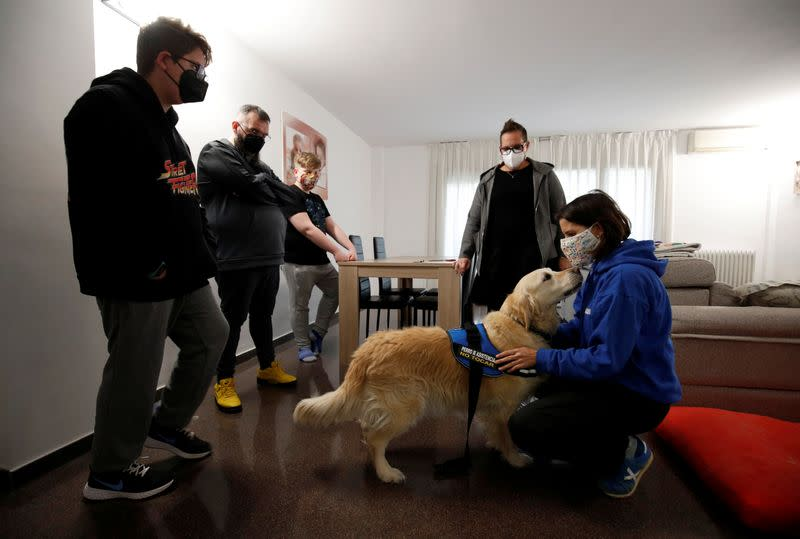 Meritxell Arias, dog-assisted intervention technician and AAS DISCAN founder, salutes dog assistant Niko during her visit to Hector Aguera and family in Terrassa