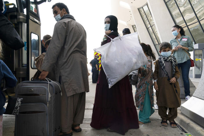 Children accompanied by their families evacuated from Kabul, Afghanistan, board a bus after they arrived at Washington Dulles International Airport, in Chantilly, Va., on Friday, Aug. 27, 2021. (AP Photo/Jose Luis Magana)