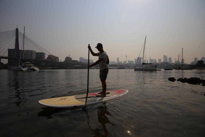 A man on a paddle board in Blackwattle Bay as smoke haze from bushfires hangs over the CBD during hot weather in Sydney.