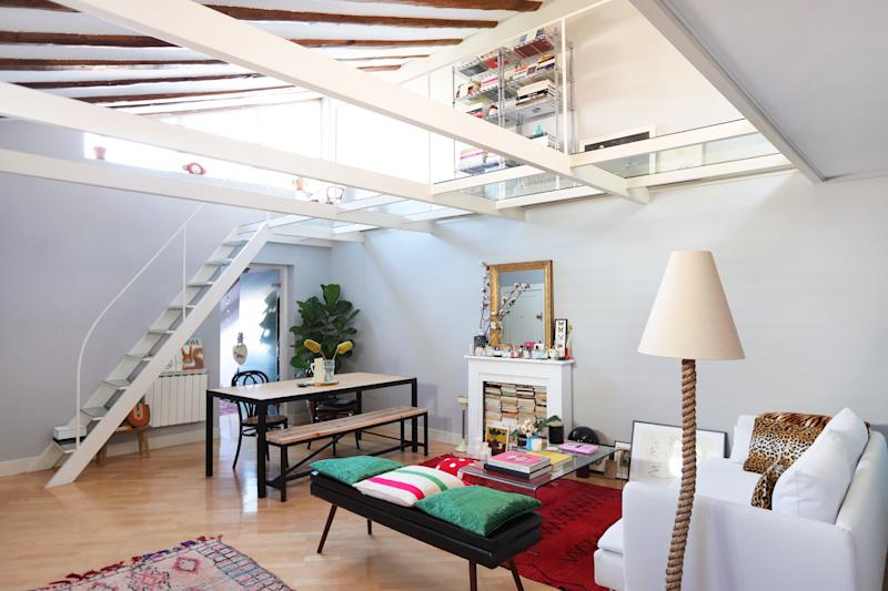 The loft's white wooden beams and glass walkway upstairs bring a whimsical dimension to the space.