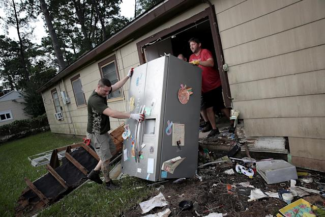 <p>Chris Gaspard (R) and Derek Pelt (L) help remove a refrigerator and other ruined items from their friend Bryan Parson's home following flooding in the wake of Hurricane Harvey September 1, 2017 in Dickinson, Texas. Dickinson was hit by Hurricane Harvey extremely hard with major flooding in many areas of the city and residents there are beginning the long process of recovery from the storm. (Photo: Win McNamee/Getty Images) </p>