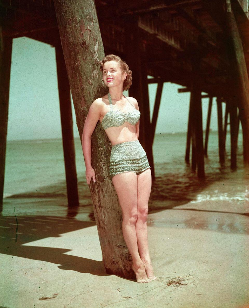 <p>American actress and singer Debbie Reynolds leans against a wooden pier post at the beach, circa the 1950s.</p>