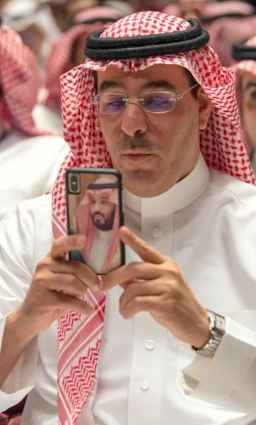 Saudi Information Minister Awwad Alawwad takes a picture at the AMC cinema in Riyadh, with the back of his cell phone showing a portrait of Crown Prince Mohammed bin Salman